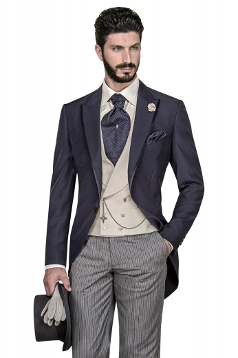 Must buy mens handmade tailed tuxedo in cashmere wool. Features a made to measure dark blue jacket, a bespoke camel vest, and handmade grey dress pants with black stripes. The mens custom made slim fit jacket features 1 front close button, 2 peak lapels with 1 boutonniere on the left lapel, and 1 upper welt pocket. The mens double breasted vest has a shawl collar and 6 front buttons, 3 to close. The mens bespoke slim fit dress pants feature a 2 point button and hook closure and a zip fly for comfort like never before.