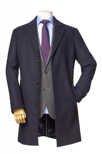 This super elegant mens tailor made dark blue wool overcoat with a single breasted pattern and 3 front close buttons is a stunning formal winter jacket that you can wear to work daily. With a display of trendy hand moulded shoulder and a comfortable finish, this mens bespoke dark blue overcoat also features 2 3-inch-wide edge stitched notch lapels with a boutonniere on the left lapel and 2 slanted edge stitched lower pockets on the front. Buy this mens handmade comfortable overcoat at My custom Tailor at affordable rates.